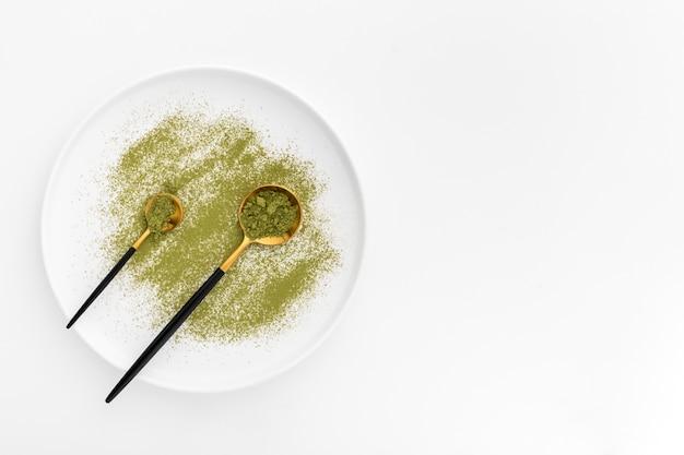 Vista superior cucharas con polvo de matcha en un plato Foto gratis