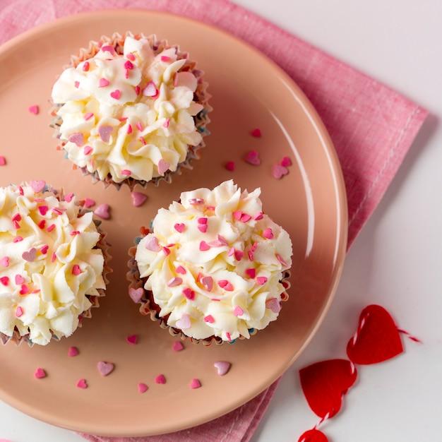 Vista superior de cupcakes con chispas en forma de corazón y glaseado Foto gratis