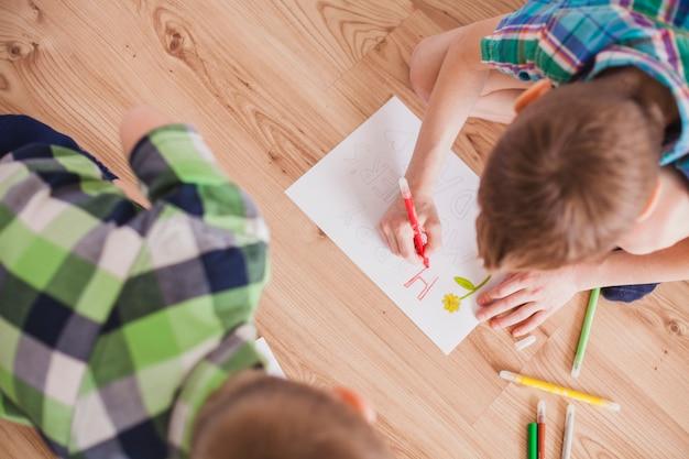 Vista superior de niño dibujando para el día de la madre Foto Gratis