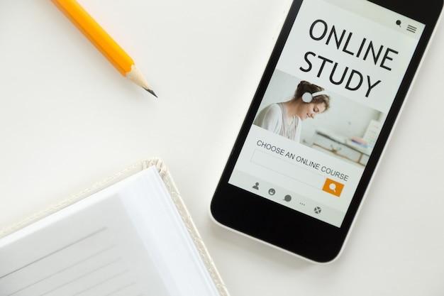 Vista superior de un teléfono móvil en el escritorio de la oficina, el estudio en línea Foto Gratis