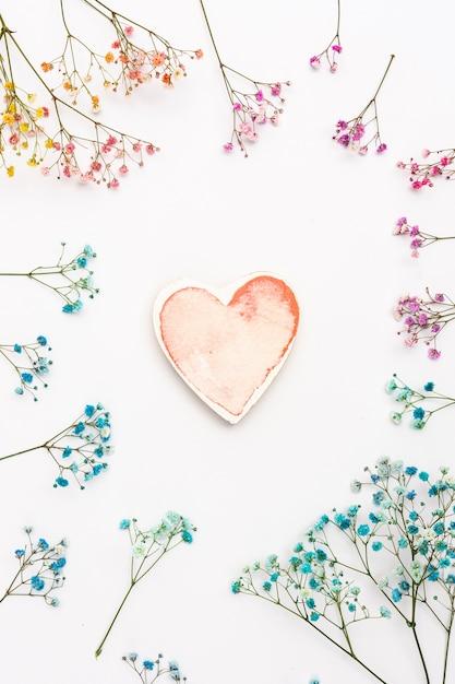 Vista superior decoración con forma de corazón y flores. Foto gratis