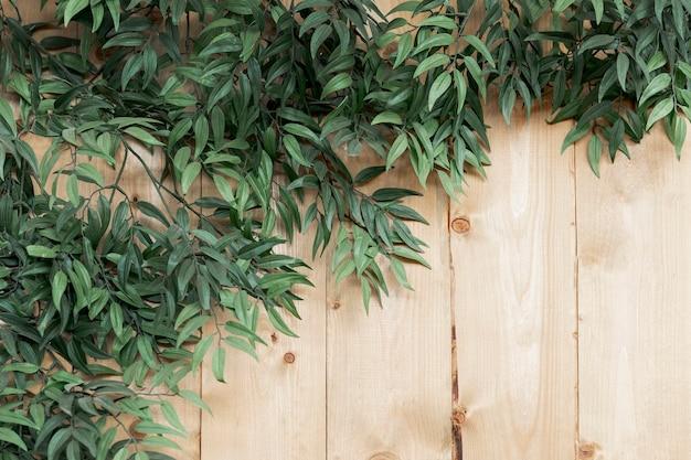 Vista superior decoración con hojas sobre fondo de madera Foto gratis
