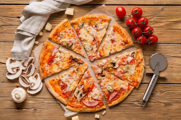 Vista superior de deliciosa pizza en mesa de madera Foto gratis
