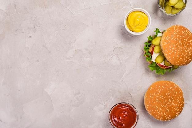 Vista superior deliciosas hamburguesas de carne con salsa de tomate y mostaza Foto gratis