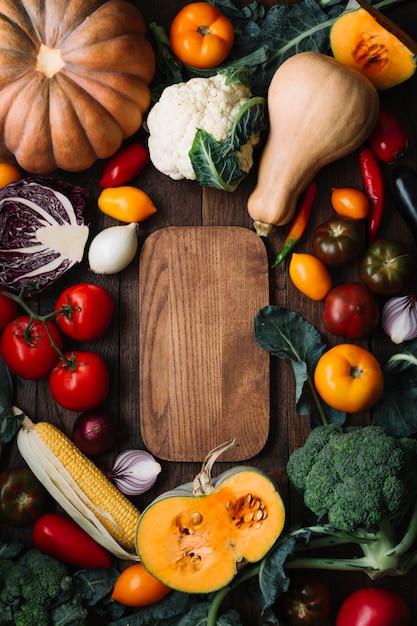 Vista superior delicioso arreglo de verduras con tabla de cortar Foto gratis