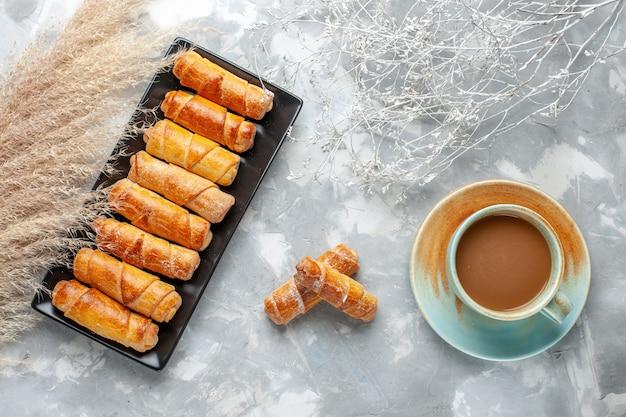 Vista superior de deliciosos brazaletes horneados dentro de molde negro con café con leche en gris, pastelería hornear galletas dulces Foto gratis