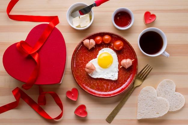 Vista superior del desayuno romántico con café y huevo en forma de corazón. Foto gratis