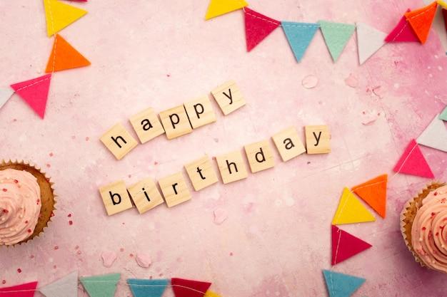 Vista superior del deseo de feliz cumpleaños en letras de madera con guirnaldas y pastelitos Foto gratis