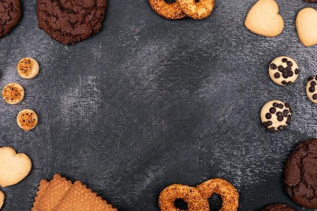 Vista superior de diferentes cookies en superficie oscura con espacio de copia Foto gratis