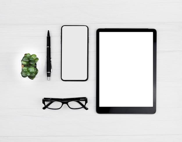 Vista superior disposición de papelería sobre fondo azul con tableta y teléfono maqueta Foto gratis
