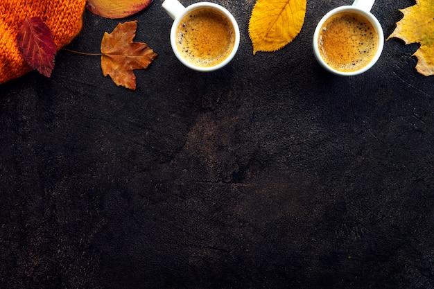 Vista superior de dos tazas de café alrededor de hojas amarillas Foto Premium