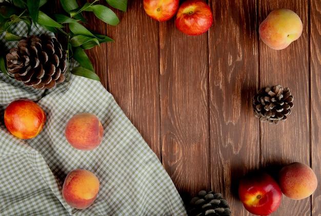 Vista superior de duraznos y piñas sobre tela en madera Foto gratis