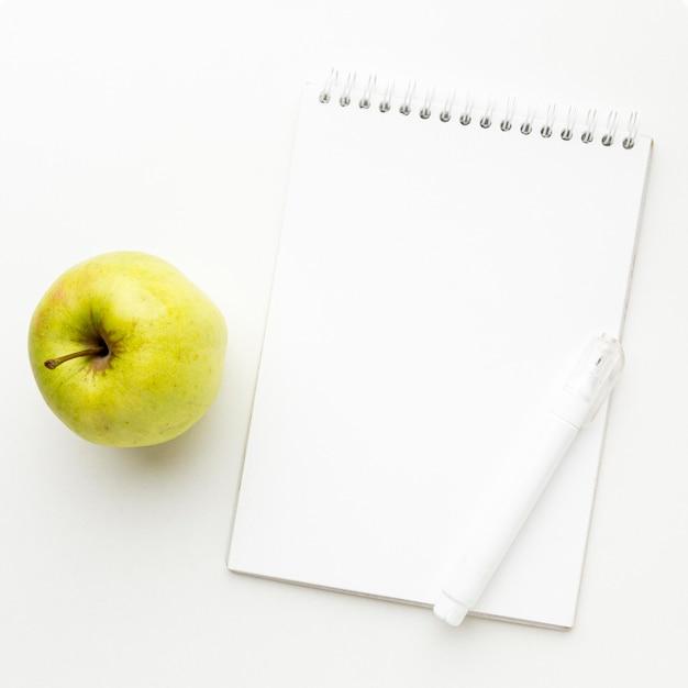 Vista superior de los elementos esenciales de regreso a la escuela con manzana y cuaderno Foto gratis