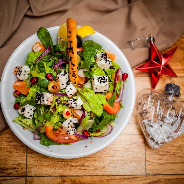 Vista superior ensalada griega con juguetes de navidad en plato redondo blanco sobre la mesa Foto gratis