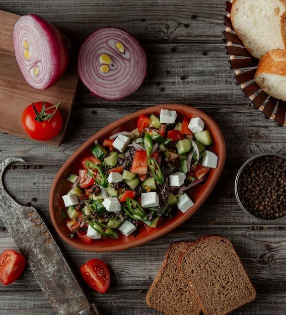 Vista superior ensalada de queso vegetal en un tazón de cerámica Foto gratis