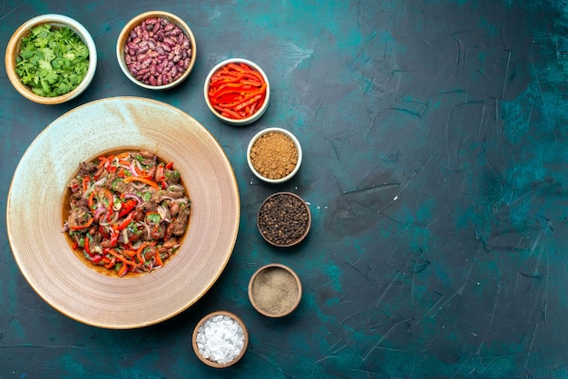 Vista superior de ensalada de verduras con frijoles verdes y condimentos sobre fondo azul oscuro ingrediente comida color vegetal Foto gratis