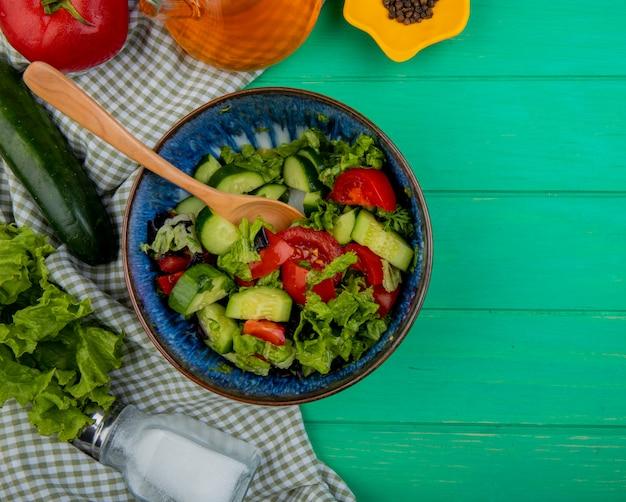 Vista superior de ensalada de verduras con lechuga tomate pepino sal y pimienta negra sobre tela y verde con espacio de copia Foto gratis
