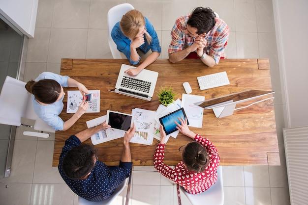 Vista superior del equipo de compañeros de trabajo trabajando en la oficina Foto gratis