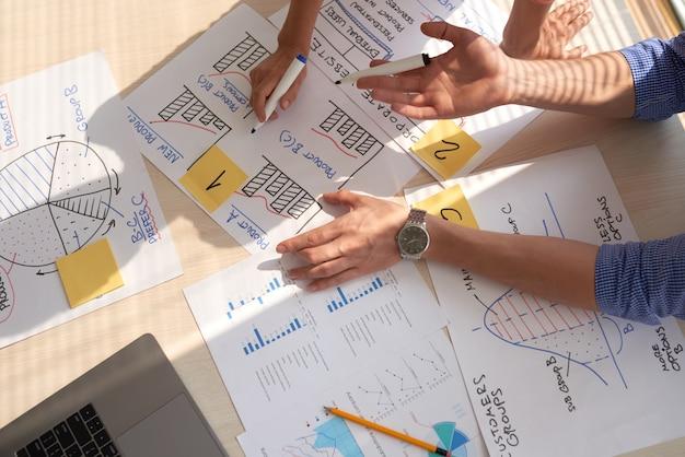 Vista superior del equipo creativo discutiendo gráficos de negocios dibujados en rotuladores Foto gratis