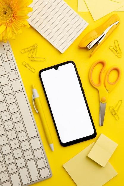Vista superior escritorio amarillo con teléfono Foto gratis