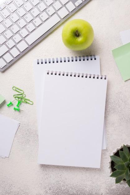 Vista superior del escritorio con cuadernos y manzana Foto gratis