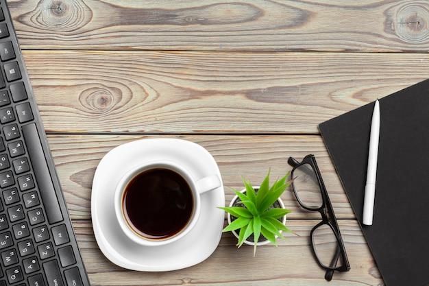Vista superior del escritorio de madera con gafas y artículos de papelería de cerca. bosquejo Foto Premium