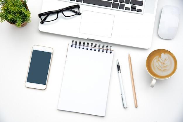 Vista superior con escritorio de trabajo con ordenador portátil, teléfono móvil, taza de café lápiz portátil y anteojos en la oficina. Foto Premium