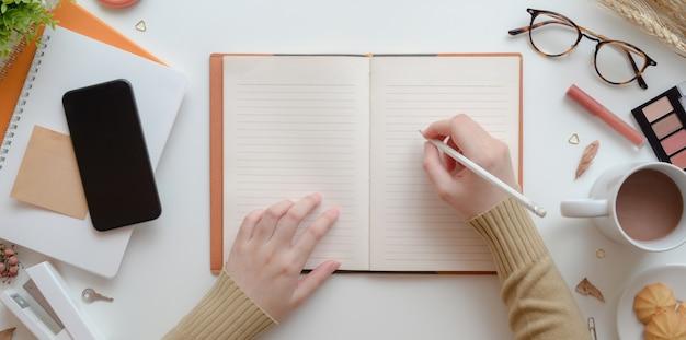Vista superior de la escritura femenina joven en el cuaderno en blanco en concepto de espacio de trabajo femenino beige cálido con maquillaje Foto Premium