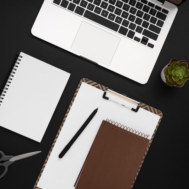 Vista superior del espacio de trabajo con bloc de notas y computadora portátil Foto gratis