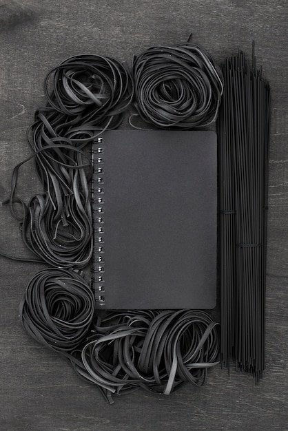 Vista superior de espagueti negro y tagliatelle con cuaderno Foto gratis
