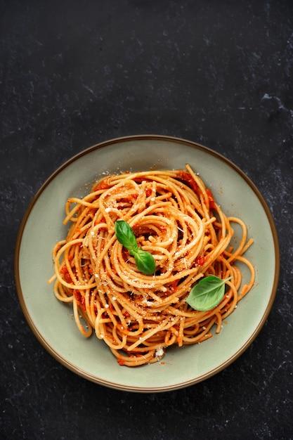 Vista superior de espagueti con salsa de tomate sobre fondo negro Foto Premium