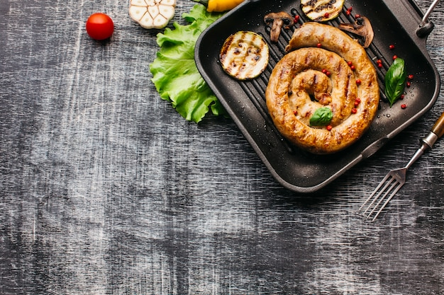 Vista superior de espiral salchicha a la parrilla con vegetales en sartén Foto gratis