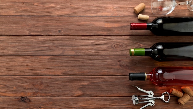Vista superior fila de botellas de vino sobre fondo de madera Foto Premium