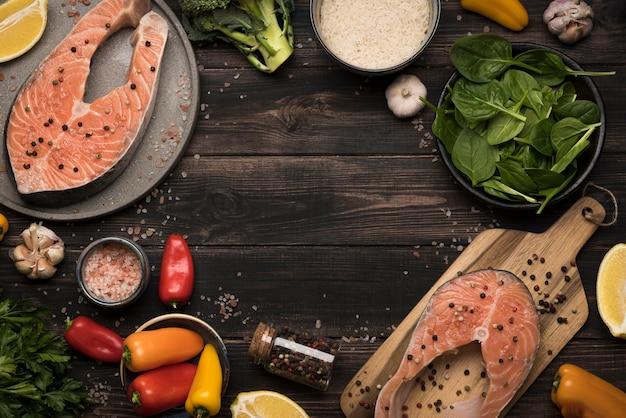 Vista superior filete de salmón crudo e ingredientes Foto gratis