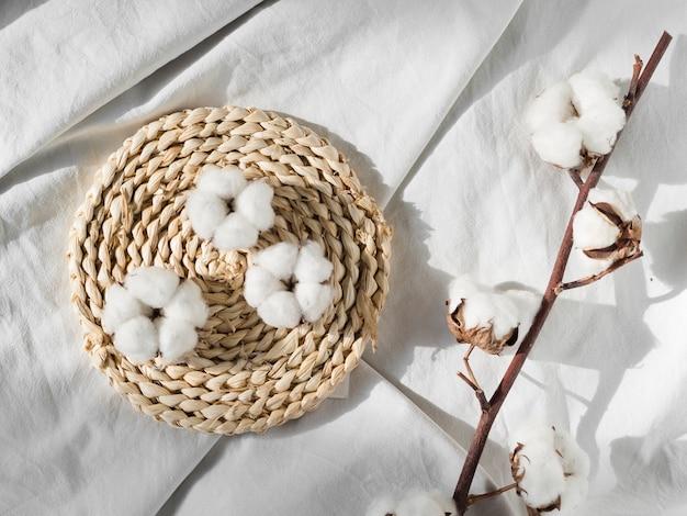 Vista superior de flores de algodón en sábana blanca Foto gratis