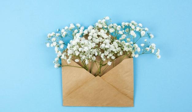 Vista superior de las flores del aliento del bebé en un sobre marrón Foto gratis