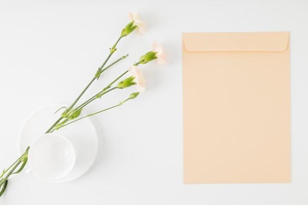 Vista superior flores con sobre y taza Foto gratis