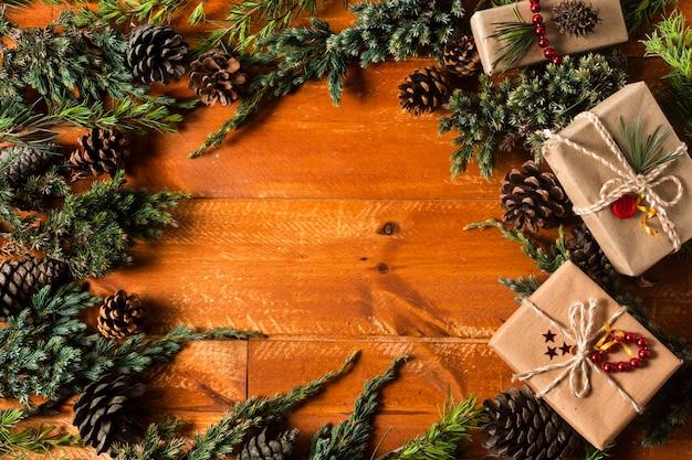 Vista superior de fondo de madera con marco de conos de árbol de navidad Foto gratis