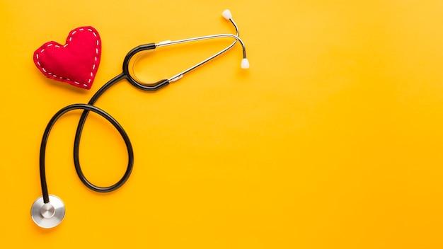 Vista superior de la forma del corazón cosido con estetoscopio sobre fondo amarillo brillante Foto gratis