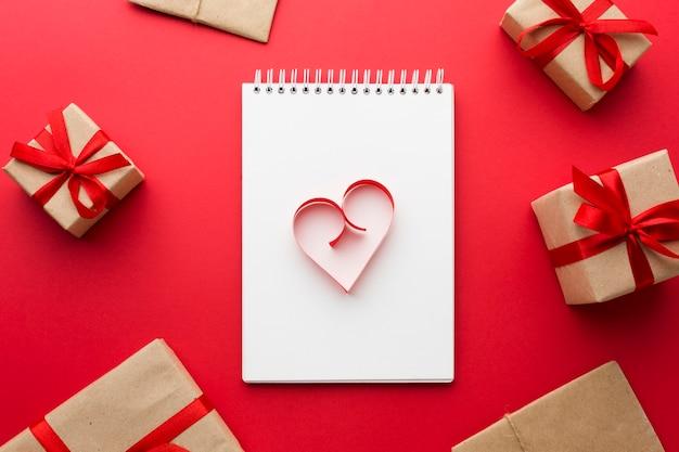 Vista superior de la forma del corazón de papel en el cuaderno con regalos Foto gratis
