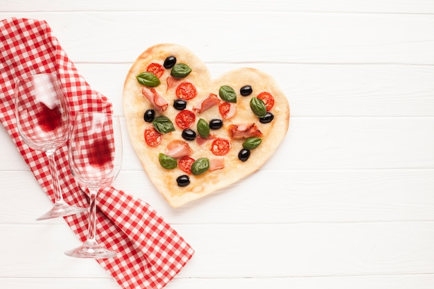 Vista superior en forma de corazón de pizza en la mesa con un paño Foto gratis