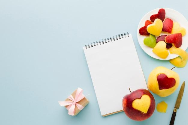 Vista superior de formas de corazón de fruta con cuaderno y presente Foto gratis