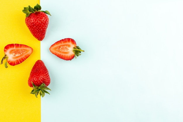 Vista superior fresas rojas jugosas suaves sobre el fondo amarillo azul Foto gratis
