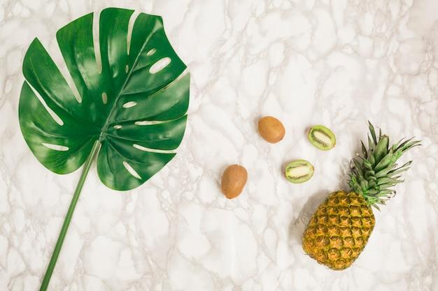 Vista superior frutas y hoja tropicales sobre mármol Foto gratis