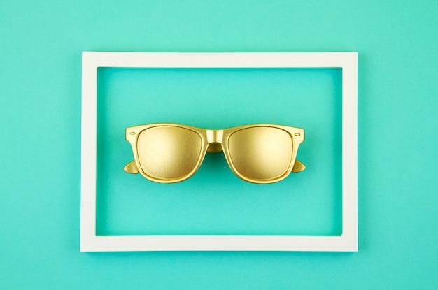 Vista superior de gafas de sol doradas de moda sobre el fondo turquesa pastel Foto Premium