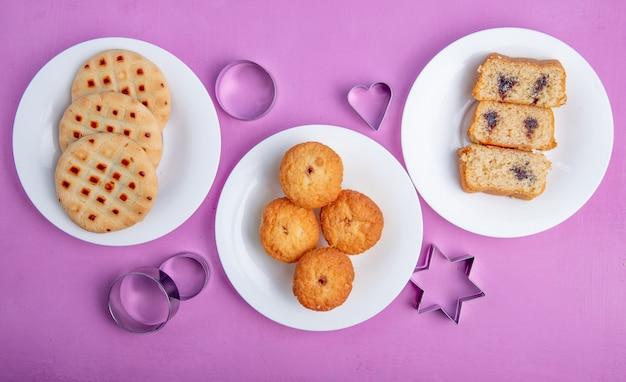 Vista superior de galletas y muffins en platos y cortadores de galletas sobre fondo morado Foto gratis