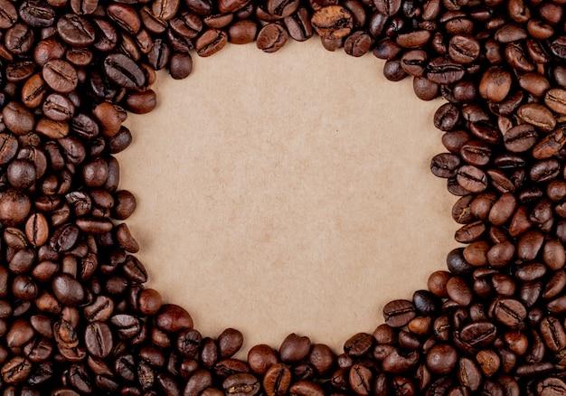 Vista superior de los granos de café círculo sobre fondo de textura de papel marrón Foto gratis