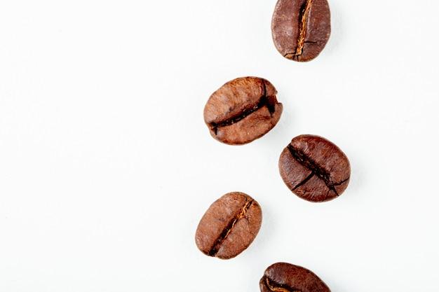 Vista superior de granos de café tostado aislado sobre fondo blanco con espacio de copia Foto gratis