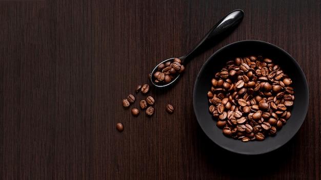 Vista superior de granos de café tostados con cuchara y espacio de copia Foto gratis