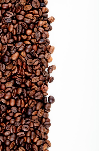 Vista superior de granos de café tostados esparcidos sobre fondo blanco con espacio de copia Foto gratis